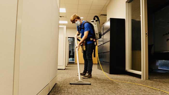 Man vacuums office space area